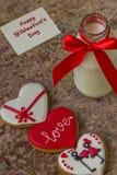Biscuits pour le jour du ` s de Valentine et bouteille en verre de lait avec le ri rouge Photos stock