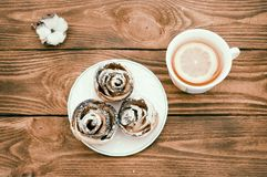 Biscuits with powdered sugar and hot tea with lemon. royalty free stock image