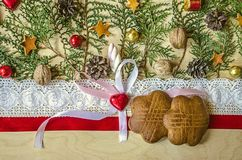Biscuits on a red ribbon and lace edging, chocolate heart with a bow and sprigs of thuja Stock Photos