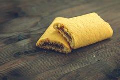 Biscuits, remplis de confiture avec des cerises sur le fond en bois de table Photographie stock