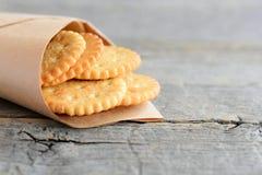 Biscuits ronds salés dans un papier d'emballage sur un fond en bois de vintage avec l'espace de copie pour le texte Casse-croûte  Images libres de droits