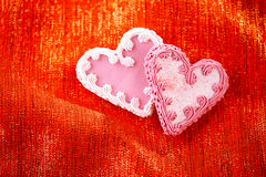 Biscuits roses blancs de fête de coeur sur le contexte rouge de scintillement Image libre de droits
