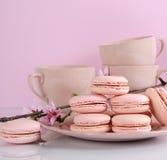 Biscuits roses de macaron avec des tasses de vintage Image libre de droits