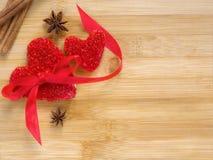 Biscuits rouges de coeur avec le ruban, un arc et l'anis d'étoile sur le fond en bois Jour de valentines et concept d'amour Images stock
