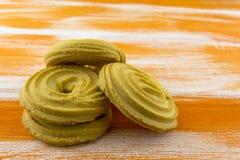 Biscuits sablés ronds se trouvant sur une table orange en bois image libre de droits