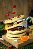 Biscuits sablés volants formés comme anneaux décorés des cerises et des écrous secs Photo stock