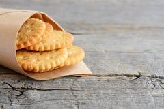 Biscuits salés délicieux dans un papier d'emballage sur un vieux fond en bois avec l'espace de copie pour le texte Biscuits savou Photographie stock