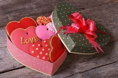 Biscuits savoureux dans la boîte en forme de coeur de valentines sur une table en bois Images libres de droits