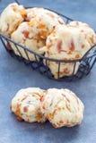Biscuits savoureux faits maison avec du fromage et le lard dans le panier et sur la table, verticale Photos libres de droits