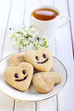 Biscuits with smile. And cup of tea Stock Photography