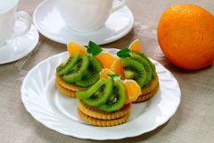 Biscuits with some pieces of kiwi fruit and orange. On the white plate royalty free stock photography