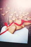 Biscuits sous forme de coeur de lettre avec le ruban rouge Photographie stock libre de droits
