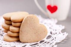 Biscuits sous forme de coeur sur un fond gris et tasse blanche à l'arrière-plan, minimalisme, un concept de la cuisson, bakin Photo libre de droits