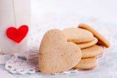 Biscuits sous forme de coeur sur un fond gris et tasse blanche à l'arrière-plan, minimalisme, un concept de la cuisson, faisant c Images stock