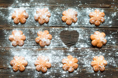 Biscuits sprinkled with powdered sugar on its surface. Horizonta. Butter biscuits brown color in the form of a flower sprinkled with powdered sugar on a dark Royalty Free Stock Photo