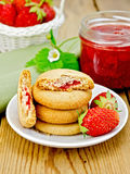 Biscuits with strawberries and a basket on the board Stock Photos