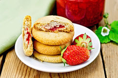 Biscuits with strawberries and jam on the board Stock Images