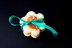 Biscuits sur les milieux noirs, attachés avec un ruban vert Image stock