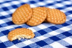 Biscuits sur une nappe checkered bleue images libres de droits