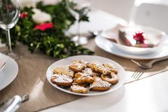 Biscuits on a table set for a dinner at home at Christmas time. Gingerbread biscuits on a table set for a dinner at home at Christmas time stock photos