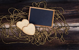 Biscuits, tableau noir et perles en forme de coeur Photo stock