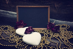 Biscuits, tableau noir et roses en forme de coeur Images stock