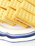 Biscuits for tea time!. A plate of delicious and crunchy looking biscuits with lemon cream sandwiched between two slices.  Appetizing golden yellow colour Royalty Free Stock Image