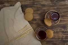 Biscuits with two glasses of tea on wooden table as chat place. Aerial royalty free stock photos