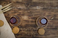 Biscuits with two glasses of tea on wooden table as chat place. Aerial royalty free stock image