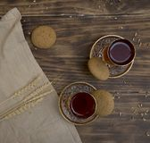 Biscuits with two glasses of tea on wooden table as chat place. Aerial royalty free stock photo