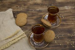 Biscuits with two glasses of tea on wooden table as chat place. Aerial stock photo