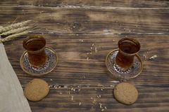 Biscuits with two glasses of tea on wooden table as chat place. Aerial royalty free stock images