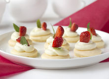 Biscuits with whipped cream, strawsberry, mint on white plate on table against light background Royalty Free Stock Photography