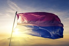 Bisexual pride flag textile cloth fabric waving on the top sunrise mist fog. Beautiful stock image