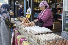 BISHKEK KIRGIZISTAN - SEPTEMBER 27, 2015: Kvinna som in säljer ägg Royaltyfri Bild