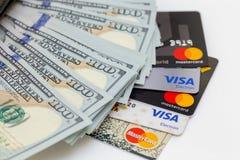Bishkek, Kirguistán - 17 de febrero de 2019: cientos billetes de dólar y tarjetas de crédito visa y Master Card en el fondo blanc foto de archivo