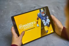 Madden nfl on ipad. Bishkek, Kyrgyzstan - January 21, 2019: Girl playing a mobile game madden nfl of ea sports company on ipad pro stock photography