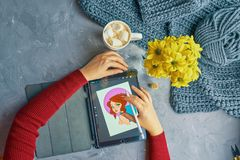 Drawing on ipad pro. Bishkek, Kyrgyzstan - January 21, 2019: Woman Illustrator draws a portrait of a girl on an iPad Pro in procreate using stock photos