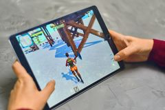 Fortnite Gameplay on ipad. Bishkek, Kyrgyzstan - January 21, 2019: Woman playing fortnite game of epic games company on Apple ios tablet iPad Pro royalty free stock photos