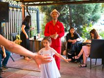 Mexican party. Bishkek, Kyrgyzstan - June 30, 2017: Little girl in white dress dancing. Man in red costume dances. Mexican party stock photo