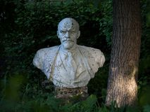 Lenin monument stands under a tree in the yard, among the usual apartment buildings. stock photography