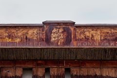 Post-Soviet roof facade with a portrait of Lenin, an abandoned and rusty industry in some of the villages of Kyrgyzstan. stock photo