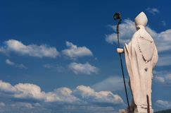 Bishop statue with clouds. Bishop with crosier, blue sky and clouds. White marble statue on Lucca old walls, erected in the 17th century with copy space Stock Image