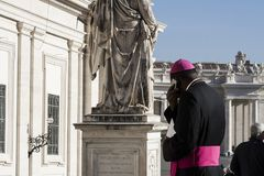 Bishop in Vatican square talking on the phone. A bishop walks and bishop speaks on the phone at Saint Peter`s Square in Vatican City, Vatican royalty free stock images