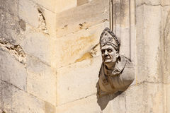Bishop on Wall. Stone carving of a bishop on the outside wall of Winchester Cathedral stock photo