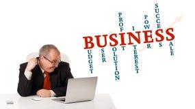 Bisinessman, das am Schreibtisch sitzt und Laptop mit Geschäft wor schaut Stockfoto