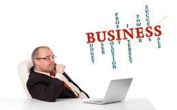 Bisinessman, das am Schreibtisch sitzt und Laptop mit Geschäft wor schaut Stockfotografie