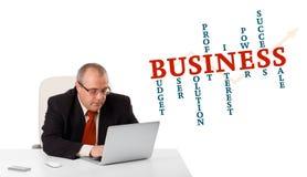 Bisinessman que se sienta en el escritorio y que mira el ordenador portátil con wor del negocio Fotografía de archivo libre de regalías