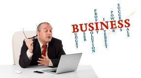 Bisinessman sitting at desk and looking laptop with business wor. D cloud, isolated on white Stock Image
