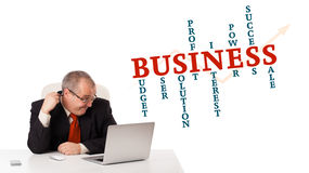 Bisinessman sitting at desk and looking laptop with business wor Stock Photo
